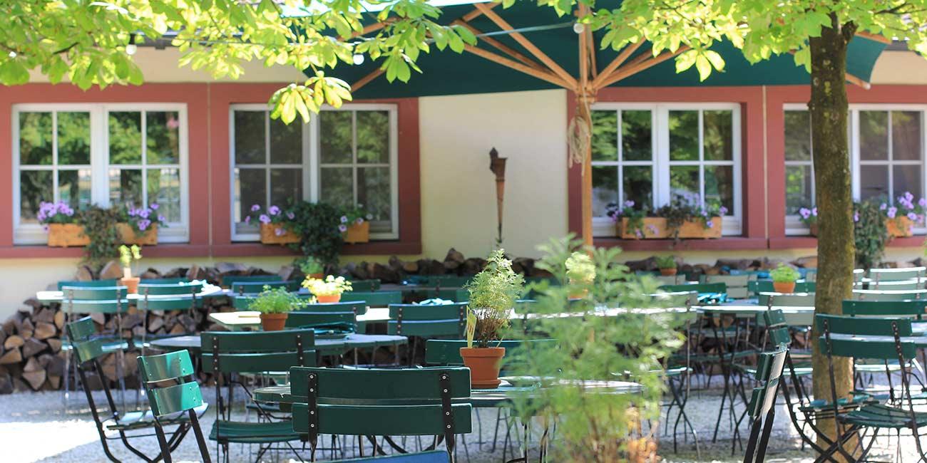 Vor einem Gebäude stehen viele Gartentische und Gartenstühle dekoriert mit Pflanzen