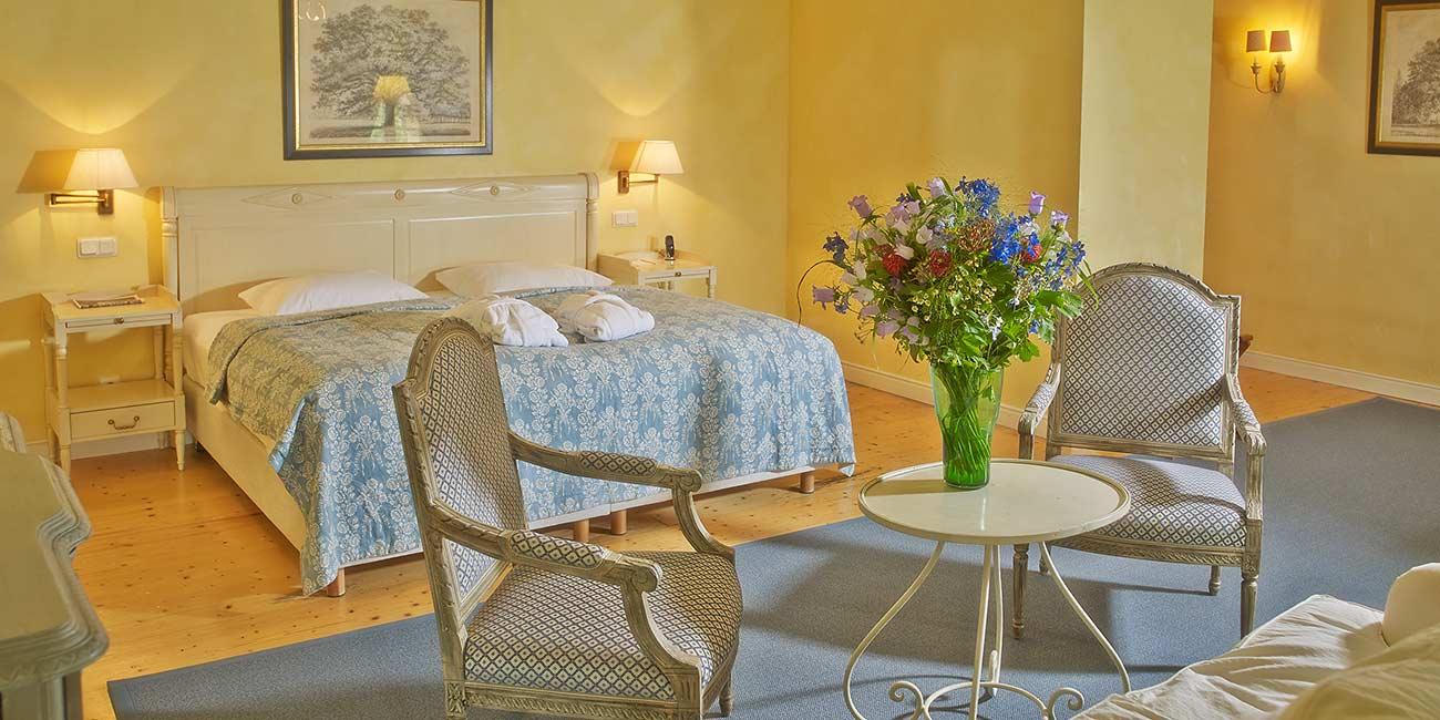 In einem gelb gestrichenen Zimmer stehen ein Tisch und zwei Stühle im Vordergrund und ein Doppelbett im Hintergrund