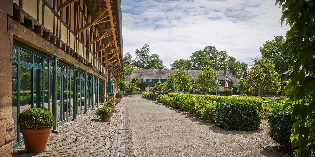 Blick auf zwei der Häuser des Gutshofs mit Grünfläche zwischen den Häusern