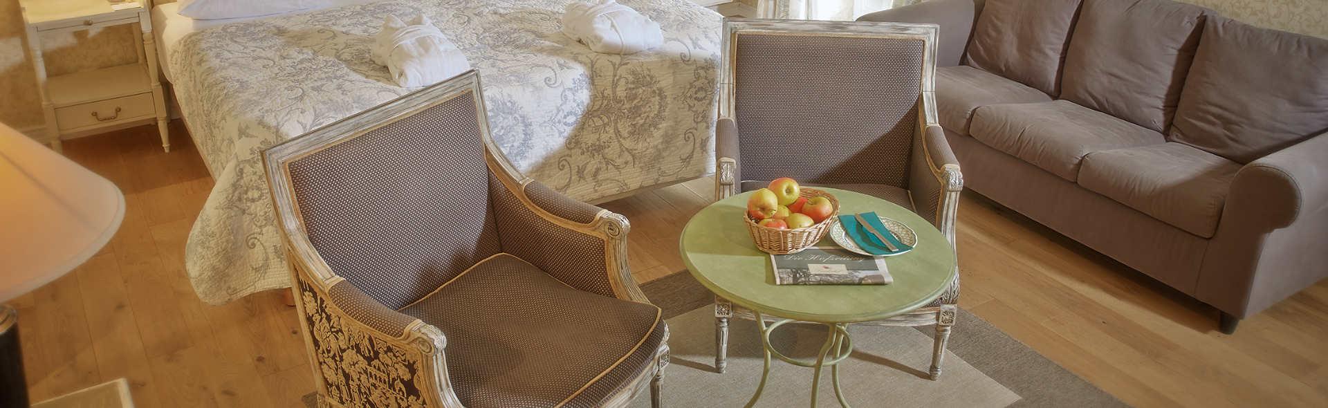 In einem Raum stehen ein Doppelbett, zwei kleine Sessel, eine Couch und ein Beistelltisch
