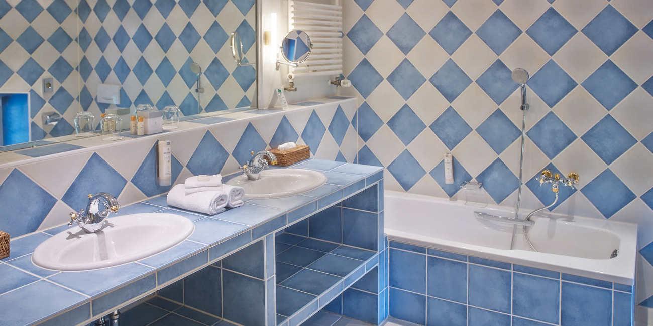 In einem blau-weoß gekachelten Bad befinden sich ein Spiegel, zwei Waschbecken und eine Badewanne