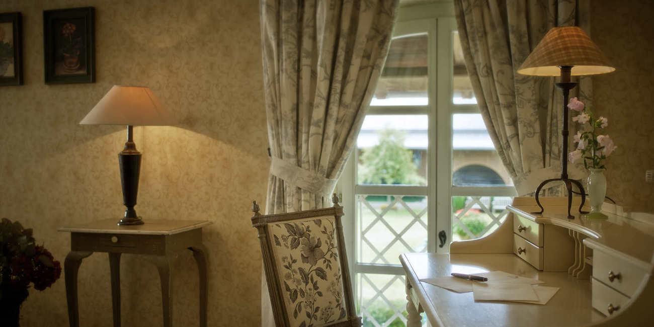 Vor einem Fenster stehen ein weißer Sekretär und ein geblümter Stuhl
