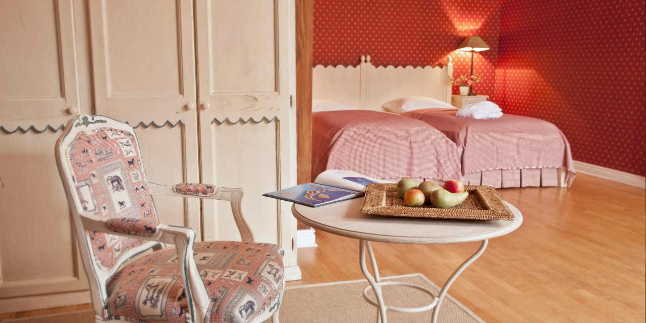 In einem großen Raum stehen zwei Einzelbetten, ein weißer Schrank, ein Tisch und ein Stuhl