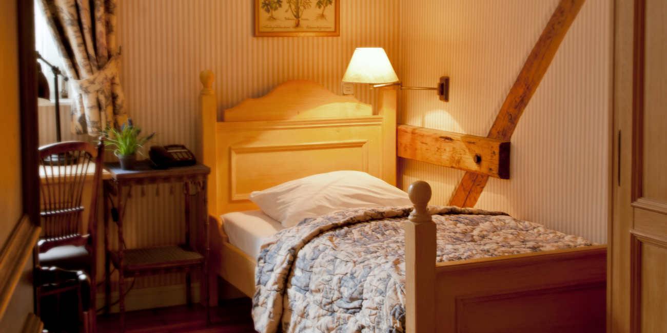 In einem Zimmer stehen ein Einzelbett, ein Nachttisch, ein Sekretär und ein Stuhl