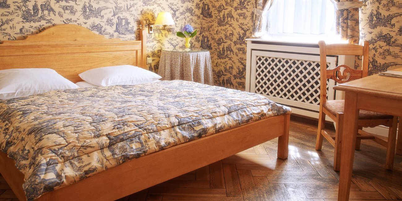 In einem Raum stehen ein Doppelbett, ein Beistelltisch, ein Tisch und ein Stuhl