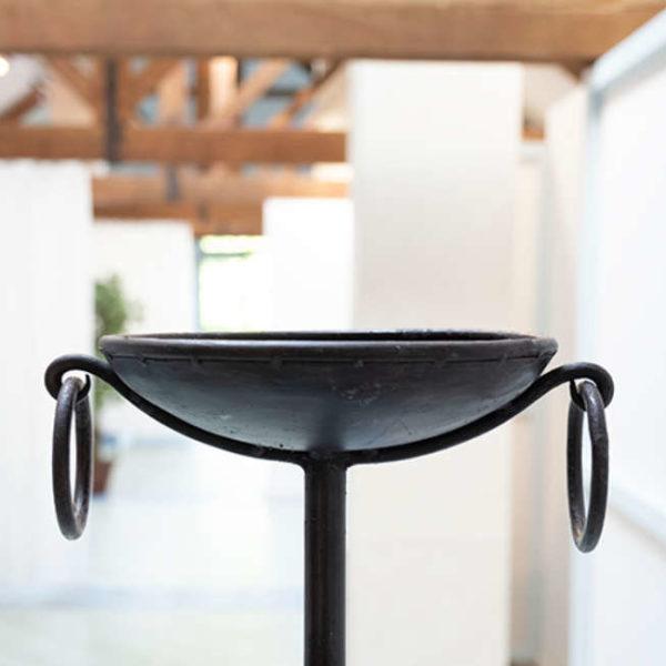 Eine gusseiserne Schale auf langem Stiel steht im Wellnessbereich des Linslerhofs