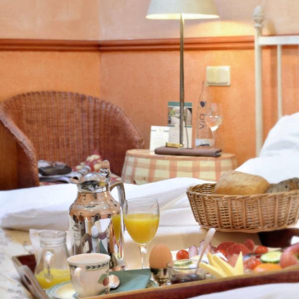 Auf einem Bett steht ein Tablett mit Frühstück