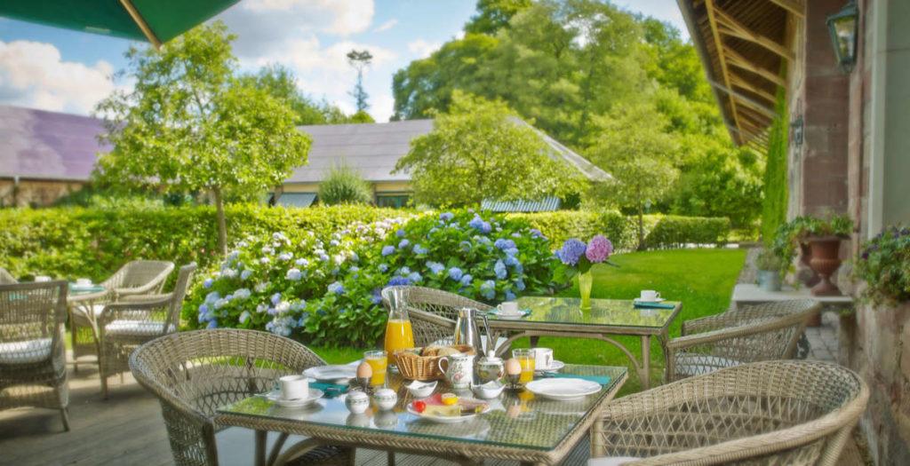 In einem Garten mit Hortensien stehen Tische, die für ein Frühstück eingedeckt sind