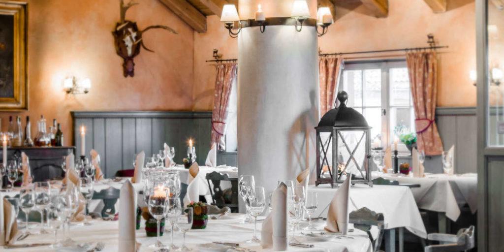 In einem rustikalen Speisesaal mit Geweihen an der Wand sind Tische elegant eingedeckt