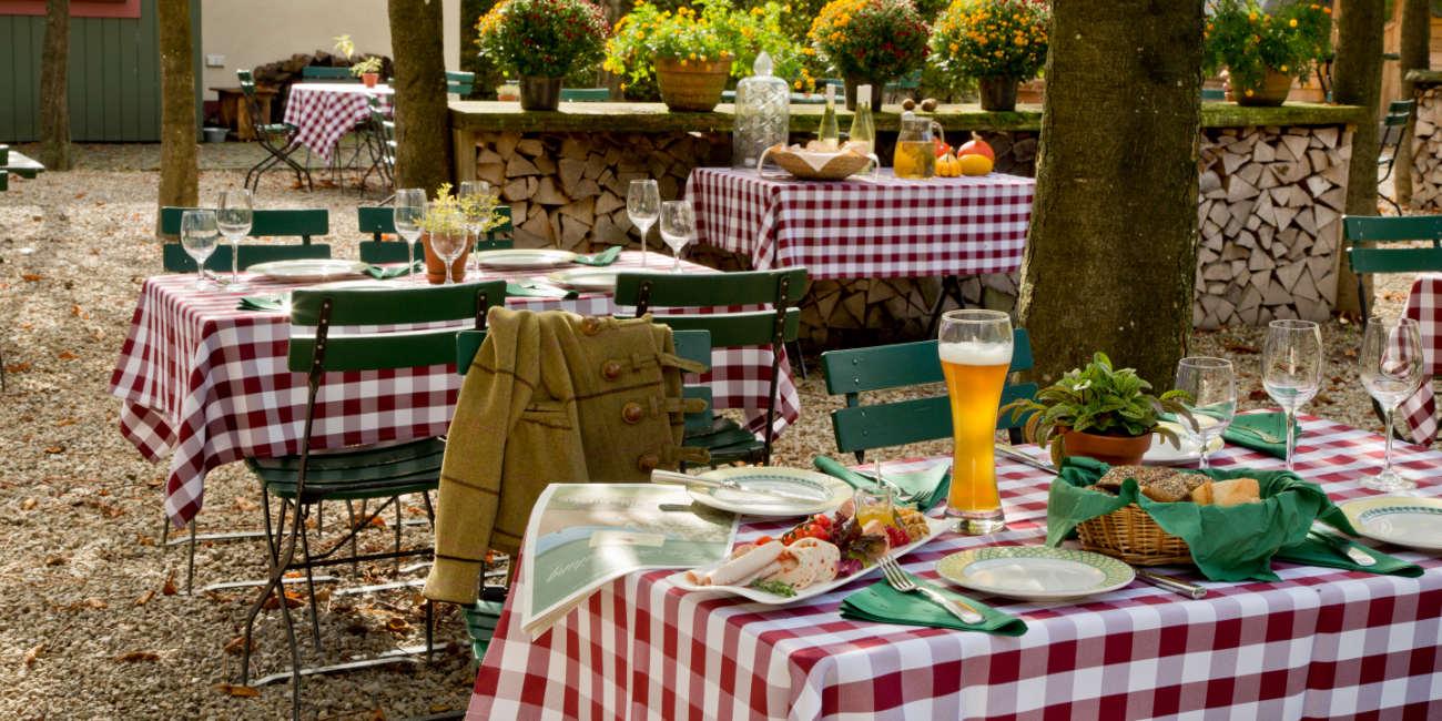 In einem Biergarten sind mehrere Tische gedeckt. Auf dem vordersten stehen Bier, Brot und diverse Beilagen