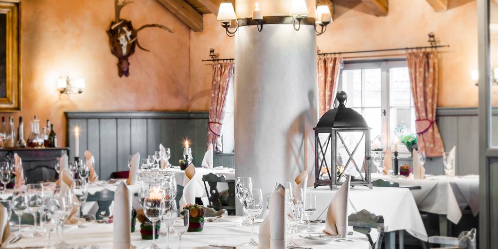 Gedeckte Tische stehen in einem hellen Raum mit offenen Dachbalken