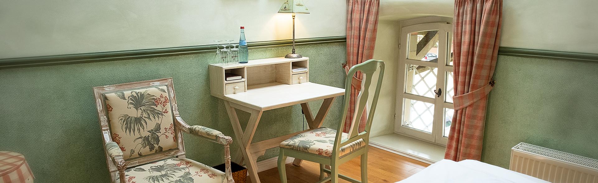 Ein Stuhl steht an einem Sekretär in einem grün tapezierten Raum