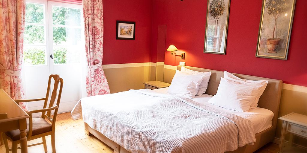 In einem in Rottönen gehaltenen Zimmer stehen ein Doppelbett sowie ein Tisch und ein Stuhl
