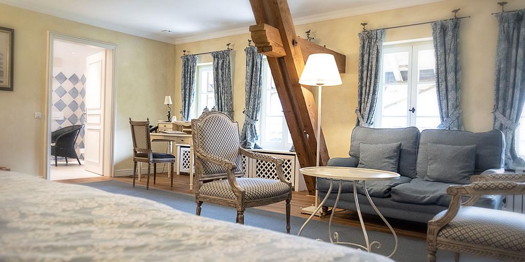 In einem großen Zimmer mit angrenzendem Raum stehen zwei Stühle, ein Sofa sowie ein Sekretär samt Stuhl