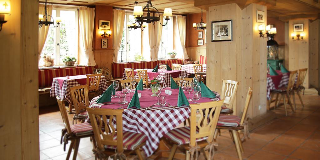In einem mit Holz verkleideten Raum stehen Stühle und gedeckte Tische mit karierten Decken