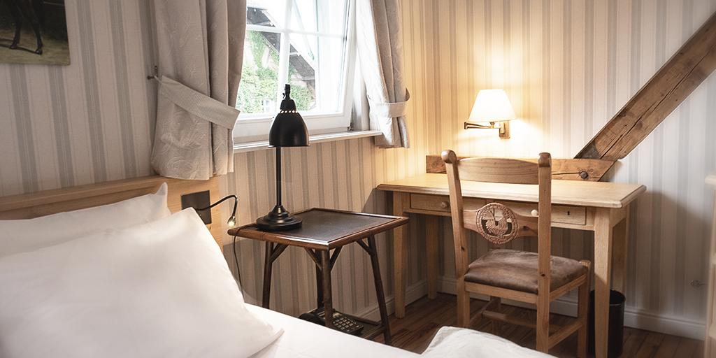 Bett, Beistelltisch, Schreibtisch und Stuhl stehen an einem gekippten Fenster