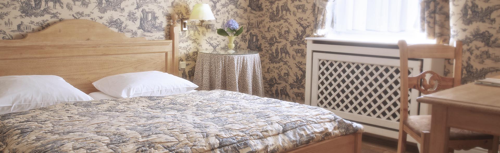 Ein Doppelbett steht in einem bunt tapezierten Raum