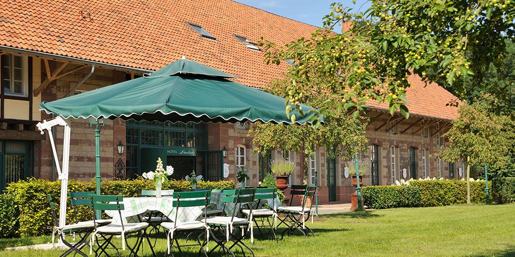 Tische, Stühle und ein Sonnenschirm stehen vor einem der Gebäude des Gutshofs