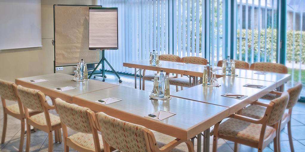 In einem Raum mit Blick ins Grüne sind Tische und Stühle U-förmig angeordnet